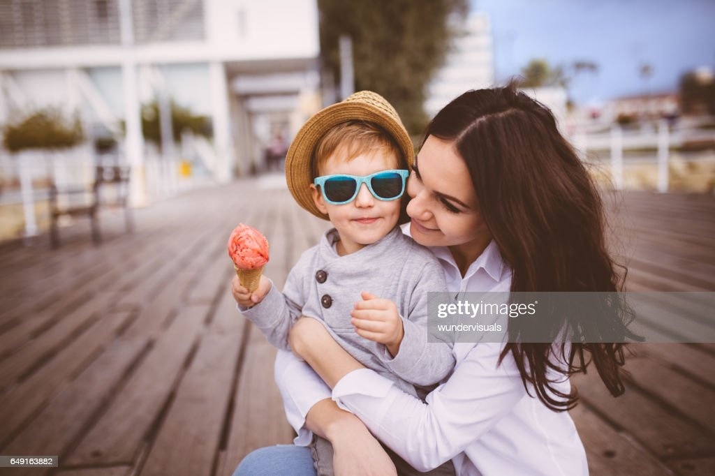 Young single mum hugging cute son who eats ice cream : Stock Photo