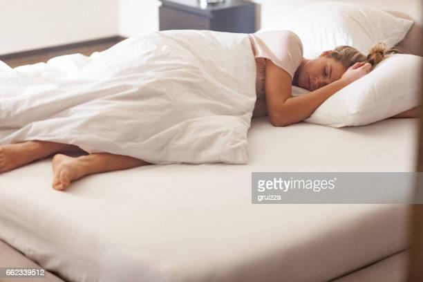 Junge alleinstehende Frau schlafend im Bett zu Hause am Morgen
