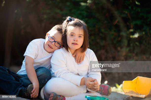 Young sister and brother with down syndrome happy outdoors
