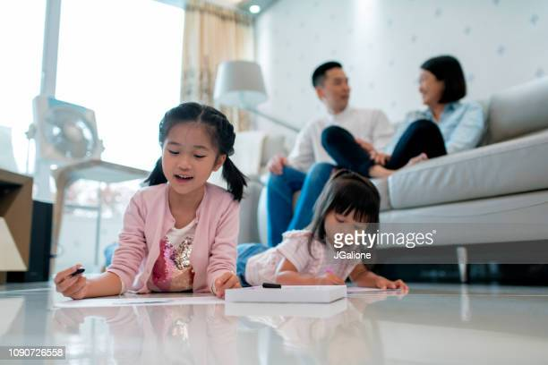 Young sisters drawing together at home