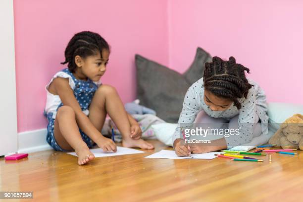 Young Sisters Drawing Together