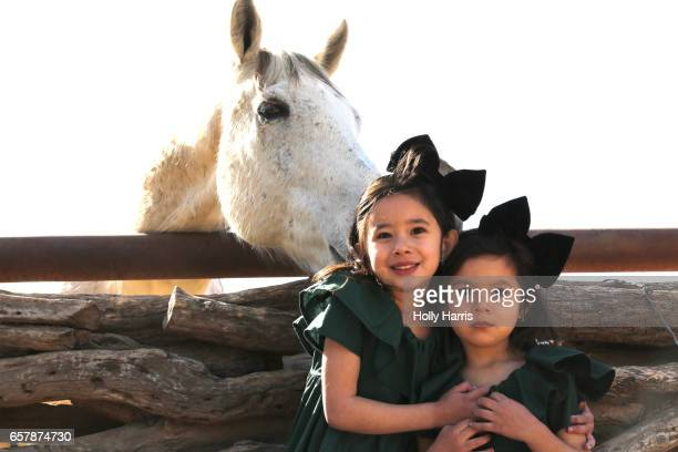 Young sisters hugging with a horse photobombing