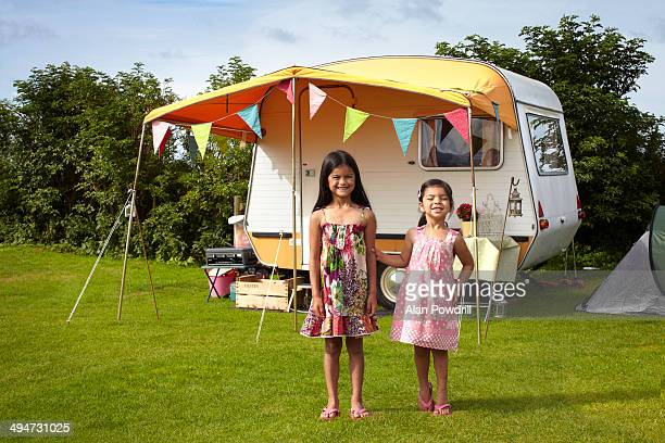 2 young sisters in front of small caravan