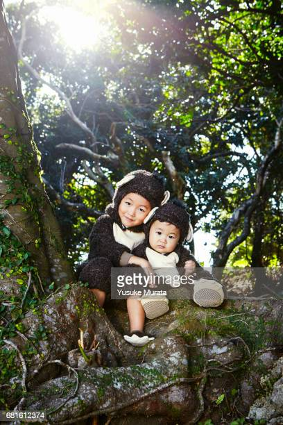 Young sisters in monkey costume on a tree