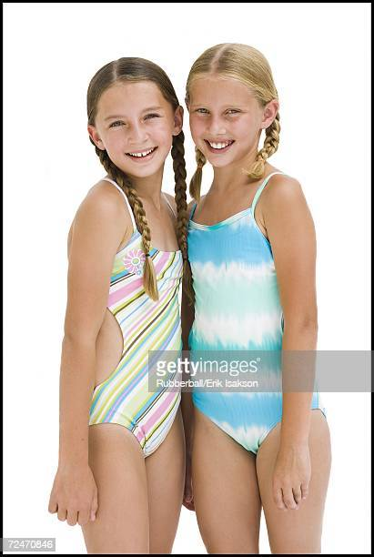 young sisters in swimsuits on vacation - one piece swimsuit stock pictures, royalty-free photos & images