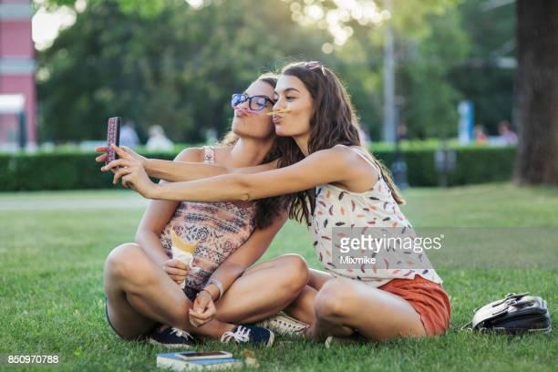Junge Schwestern im Park, Spaß haben und machen Selfies mit Handy