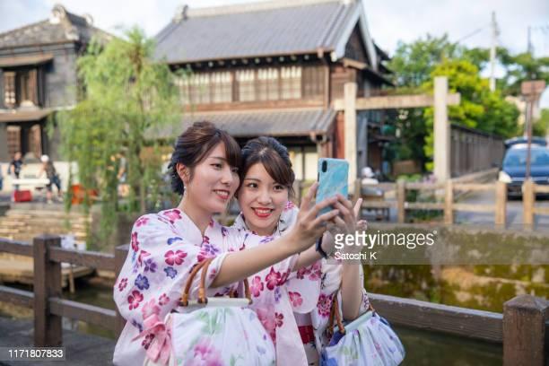 日本の伝統的な村で自撮りをする浴衣の若い姉妹 - ボン ストックフォトと画像