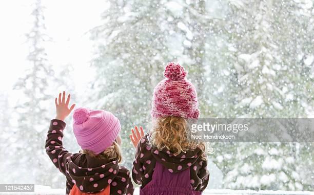 Young sisters look at snowfall outside