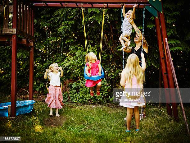 Young sisters on swings and mother holding toddler