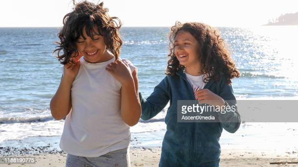 young sisters play on beach - brown hair stock pictures, royalty-free photos & images