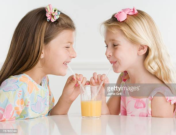 Young sisters sharing glass of juice with two straws