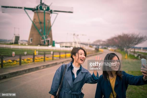 jonge zusters fotograferen selfie op tuin met windmolen - molen stockfoto's en -beelden