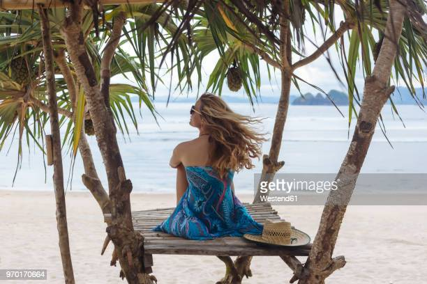 young sitting woman at the beach, looking at the sea - ロンボク島 ストックフォトと画像