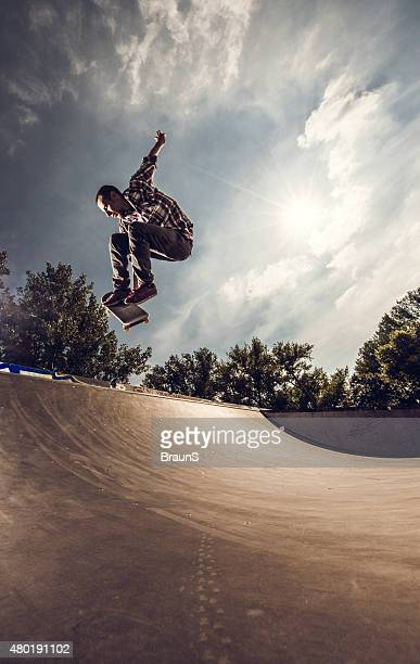 Young skateboarder practicing Ollie on a skate ramp.