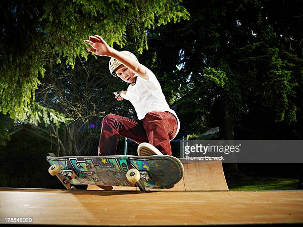Young skateboarder sliding along rail of halfpipe