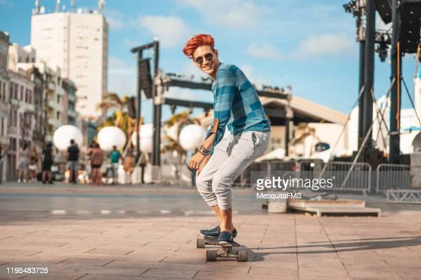junger skateboarder mit einem langen board in marco zero, recife, pernambuco. - eislauf oder rollschuhlauf stock-fotos und bilder