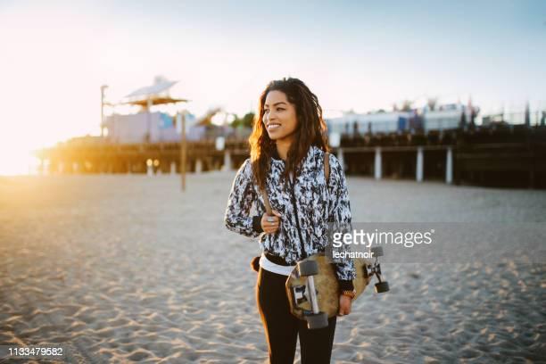 joven patinador mujer en la playa de santa mónica en la, california - santa monica los ángeles fotografías e imágenes de stock