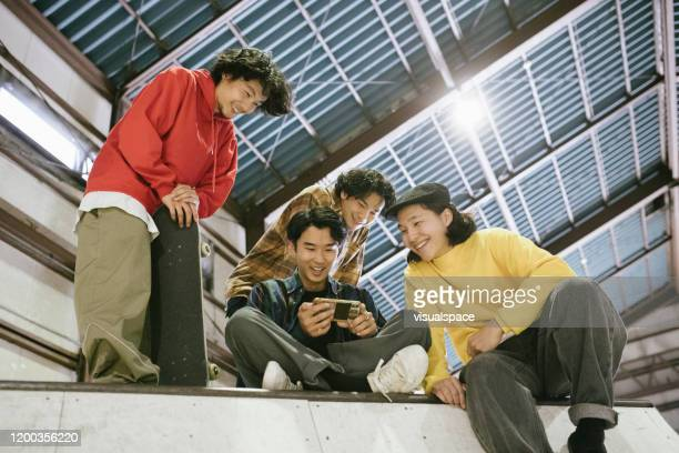 young skateboarders browsing videos from the internet - adult videos japan stock pictures, royalty-free photos & images