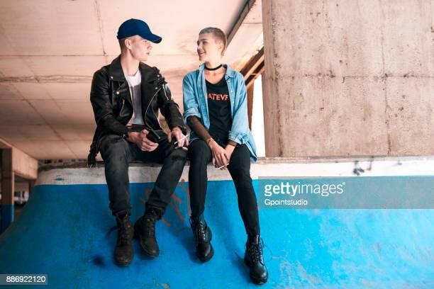 Young skateboarding couple smoking and talking on skate ramp