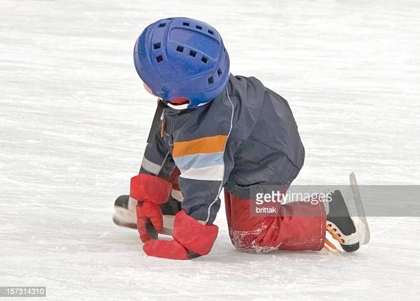 Young skater has fallen down standing on his knees.