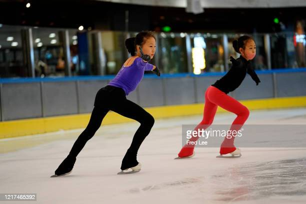 Young skaters practice during a training session with protective masks on June 3 2020 in Beijing China A free figure skating class was held in an ice...
