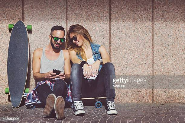 Young skaters resting and social networking with mobile