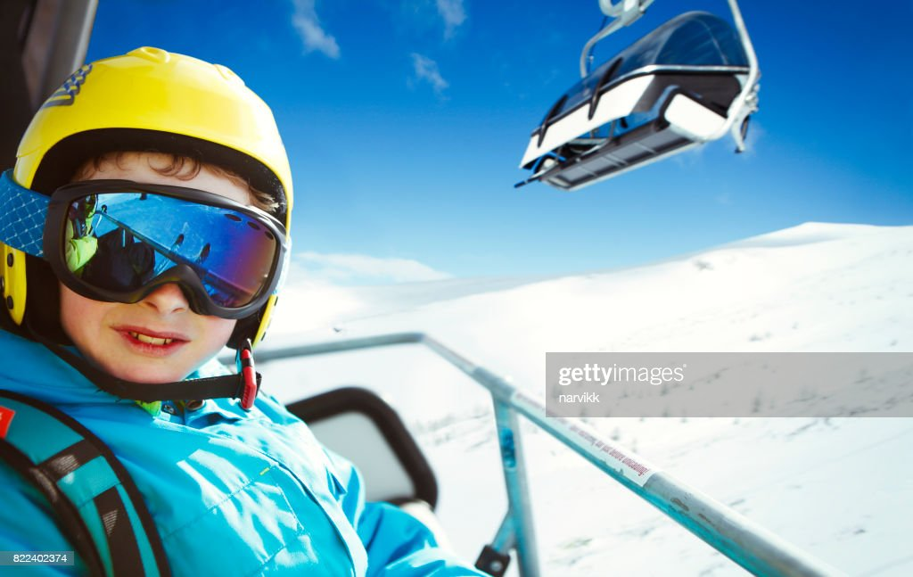 Young skier going up in the chair lift in the mountains : Stock Photo