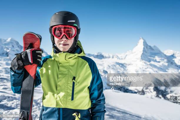 Young skier holding skis against Matterhorn mountain, Switzerland