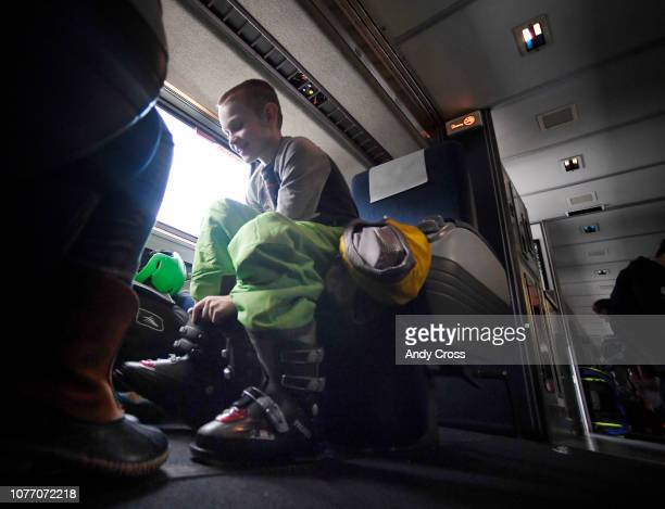 Young skier Keith Flesher puts his boots on before arriving at Winter Park on the Amtrak Winter Park Express for the train's first trip of the season...