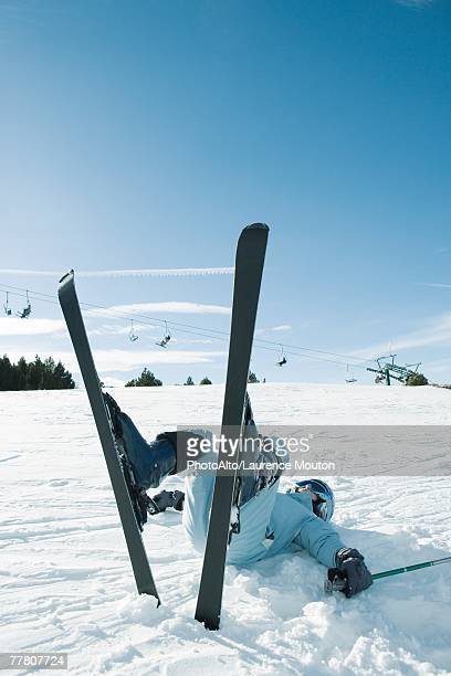 Young skier lying on back on the ground, legs in the air