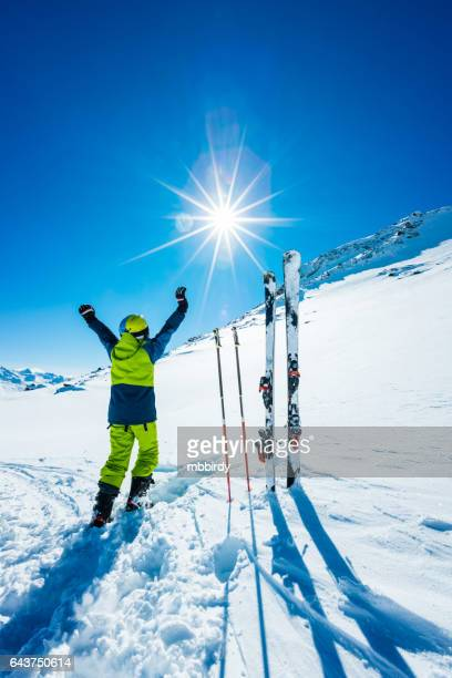 Young skier with hands in the air