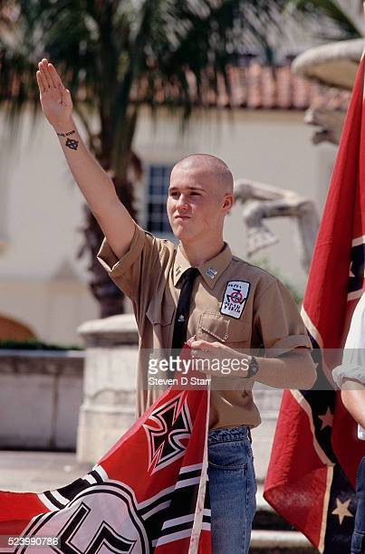 A young skinhead raises his arm in salute during a march in Palm Beach Florida Several white supremacist groups have come together for the event