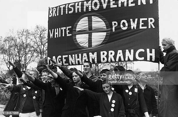 Young skinheads give a Nazi salute as they participate in a British Movement march between Paddington and Marble Arch London 1980