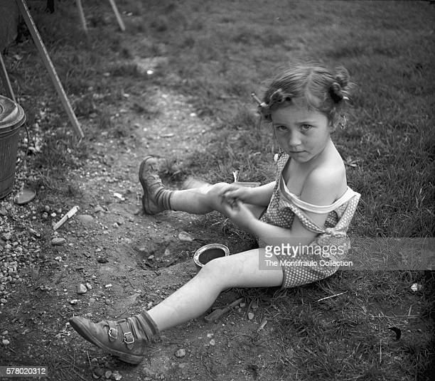 Young slightly dishevelled girl in summer dress and sandals sitting in a garden digging a small hole in the earth as she glares at the photographer...