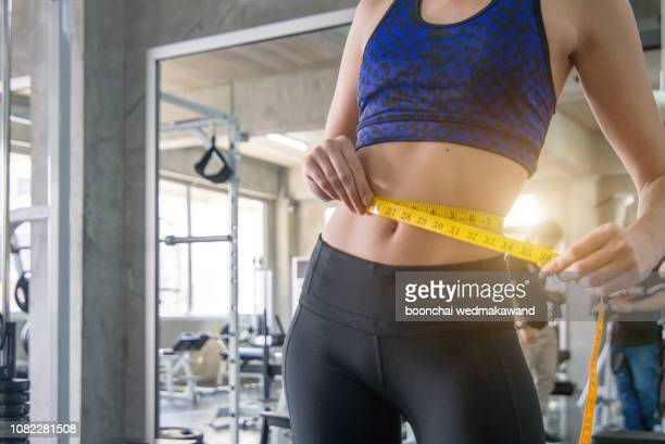 young slim woman measuring waist using the tape measure. - waist stock pictures, royalty-free photos & images