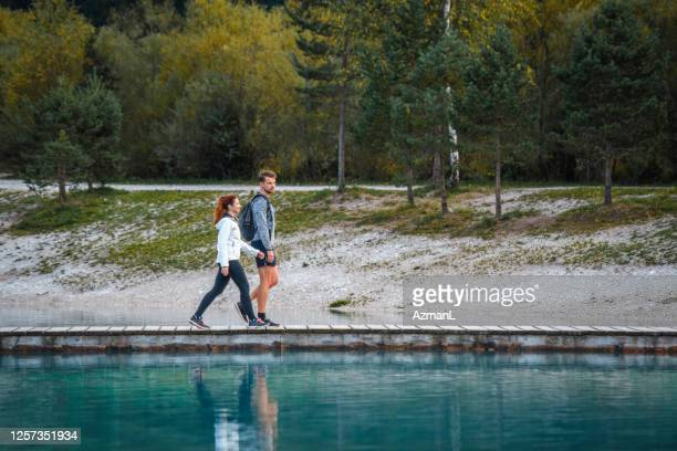 young slovenian day hikers walking on jasna lake pier - close to stock pictures, royalty-free photos & images