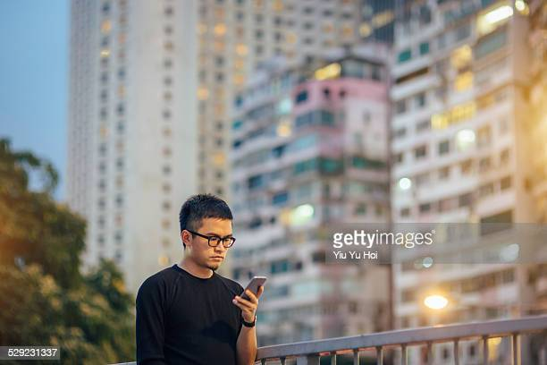 Young smart male using smartphone in city street
