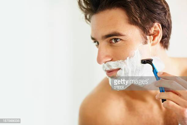 Young smart man shaving using a razor
