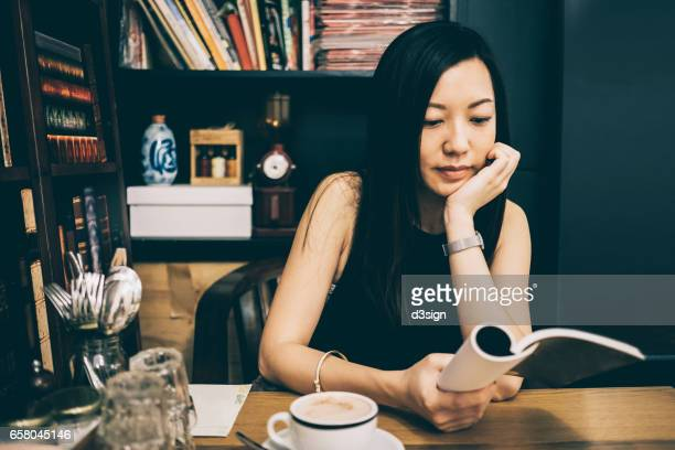 Young smiling Asian girl reading and enjoying coffee in cafe