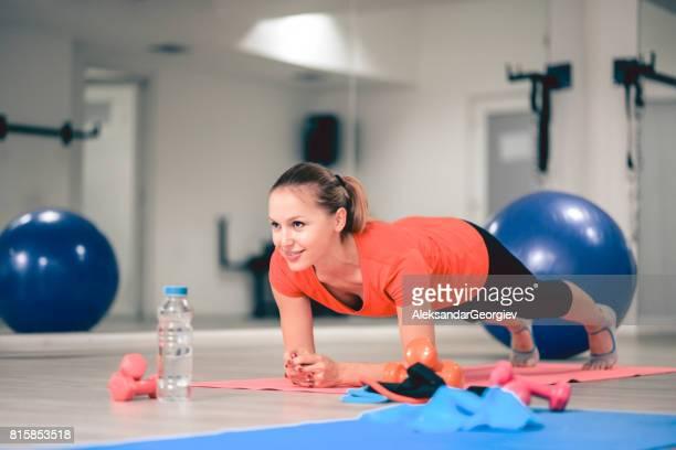 Young Smiling athlète féminin en planche poser faire Abs