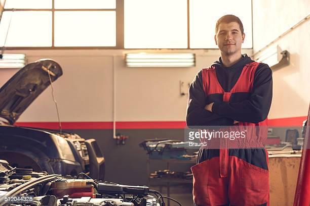 Junge lächelnd auto-Mechaniker mit überkreuzten Armen in Werkstatt.