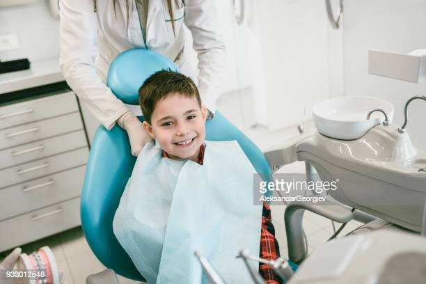 young smiling boy getting prepared for the regular dental check up in clinic - dental fear stock pictures, royalty-free photos & images