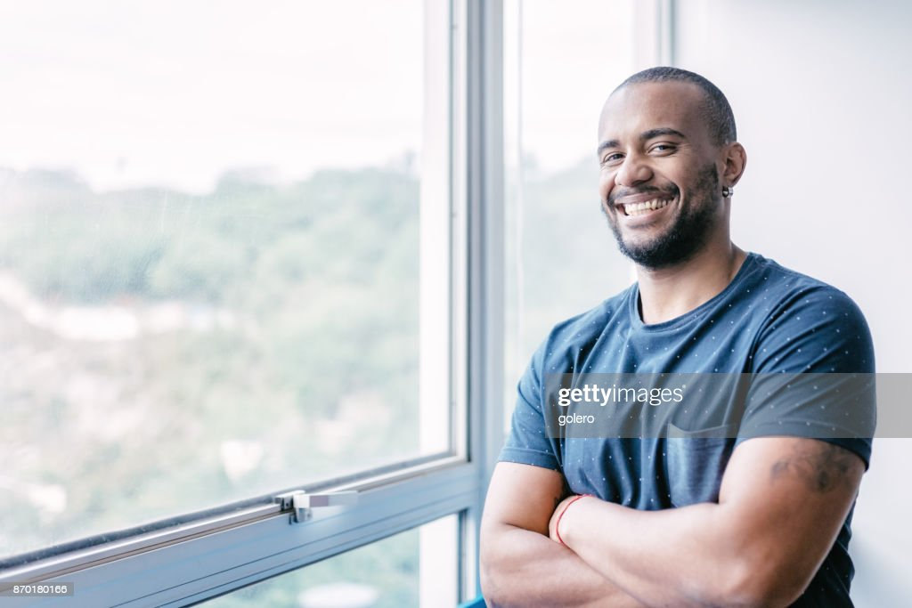 young smiling brazilian businessman at window in office : Stock Photo