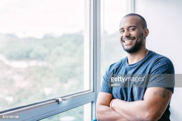 young smiling brazilian businessman at window in office - brazilian men stock photos and pictures