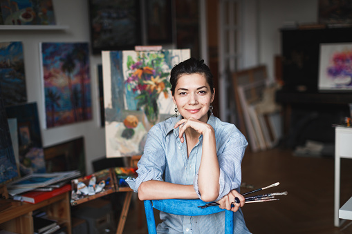 A young smiling brunette woman artist in her Studio is holding a brush. Near her easel, paintings and various art equipment. 946127028