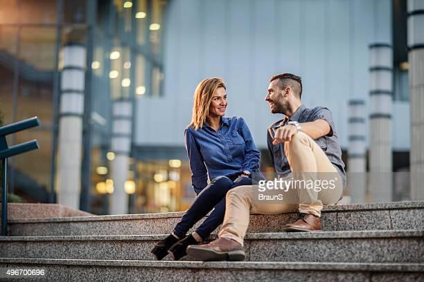 Jeune souriant couple flirts d'affaires sur l'escalier à l'extérieur.