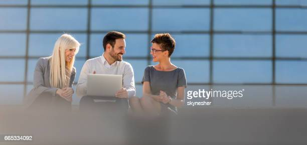 Young smiling business people using laptop together outdoors.