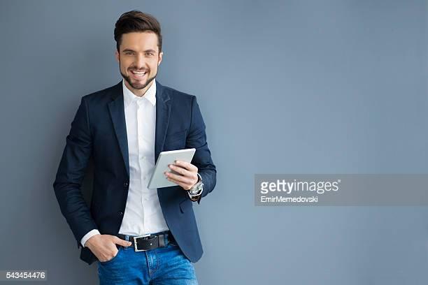 を持って笑う若い実業家デジタルタブレット、自信を持っています。