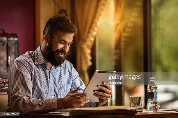 Young smiling businessman surfing the net on digital tablet.
