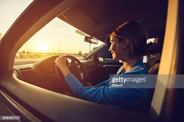 Young smiling businesswoman driving a car at sunset.